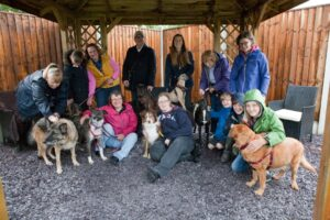 group of people with various types of dogs on leads. Under a wooden shelter