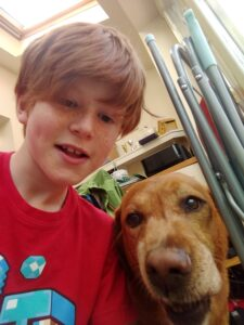 boy with ginger hair and ginger dog close together